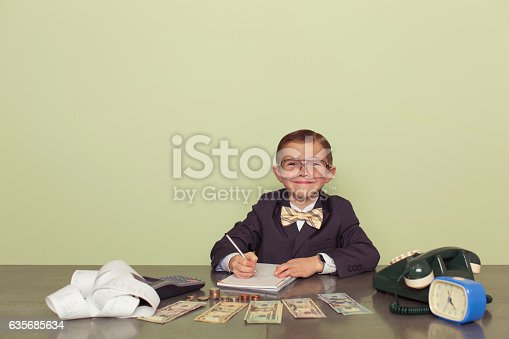 A young boy accountant and financial advisor with US dollars ready to do business and count your taxes. He is smiling while holding a pen and ready to help your business. Dressed in business suit and bow tie. Retro styled.