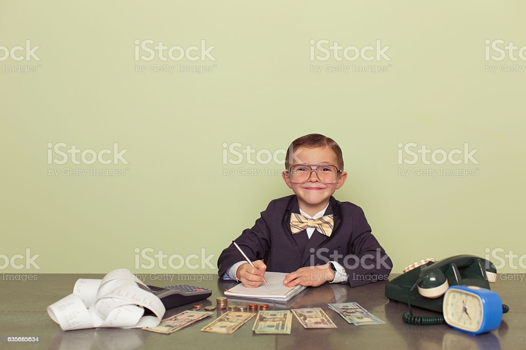 Young Boy Accountant Records Taxes to be Paid stock photo