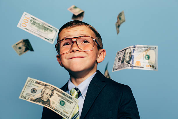 Young Boy Accountant Watches Money Fall from Sky A young boy accountant wearing glasses and suit watches U.S. currency while more falls from above. He is smiling and ready to do your taxes for the IRS and make your tax refund much more money. cheesy grin stock pictures, royalty-free photos & images