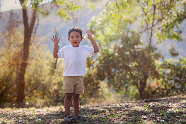 Young boy advancing to preschool age is outdoors learning to catch a ball with  his arms up in th air, in southern California setting. stock photo