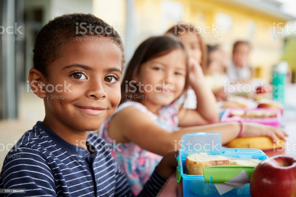 Young boy and girl at school lunch table smiling to camera royalty-free stock photo