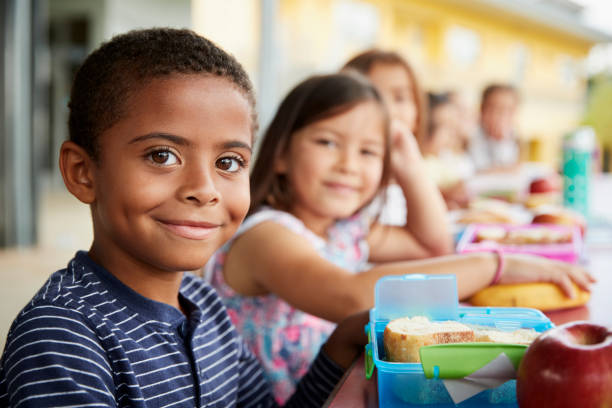 young boy and girl at school lunch table smiling to camera - school building stock pictures, royalty-free photos & images
