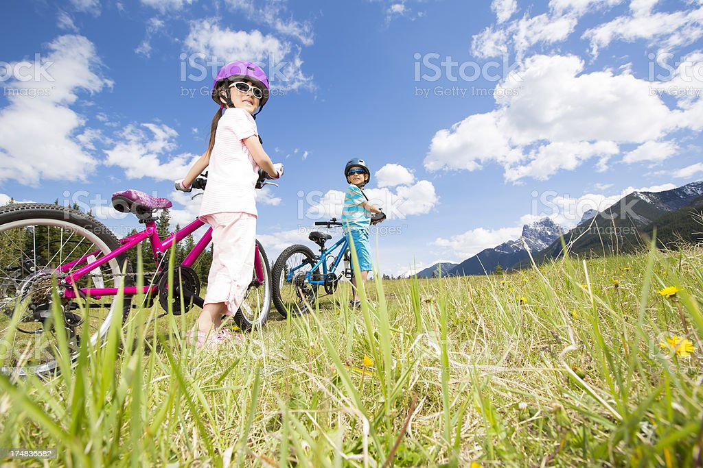 Young boy and girl enjoying the view, walking their bikes royalty-free stock photo