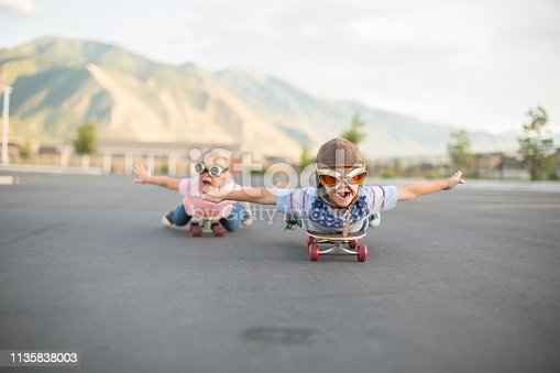 A young boy and girl wearing flight caps and goggles spread their arms out dreaming of flying while lying down on skateboards. The have excited expressions on their faces as they aspire to be pilots flying airplanes later in life. Image taken in Utah, USA.