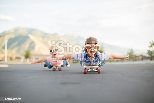 istock Young Boy and Girl Flying on Skateboards 1135839376