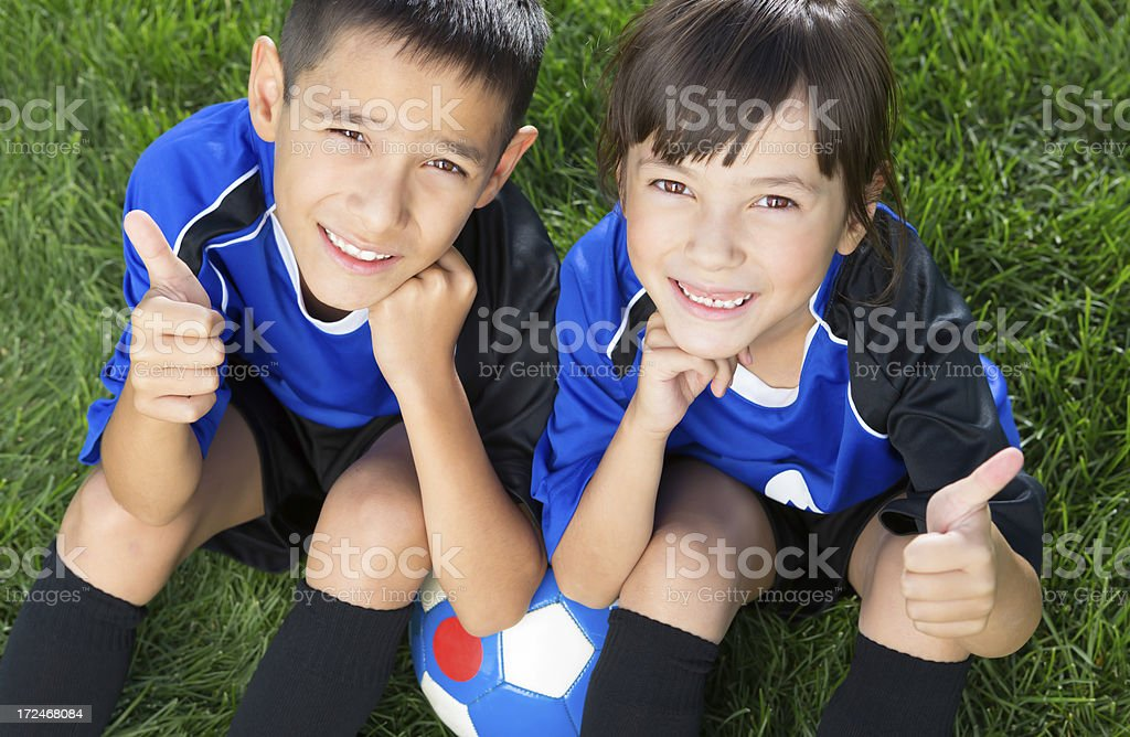 Young boy and girl giving thumbs up for soccer royalty-free stock photo