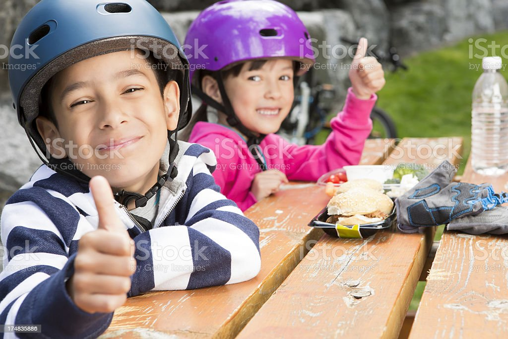 Young boy and girl giving thumbs up while eating royalty-free stock photo