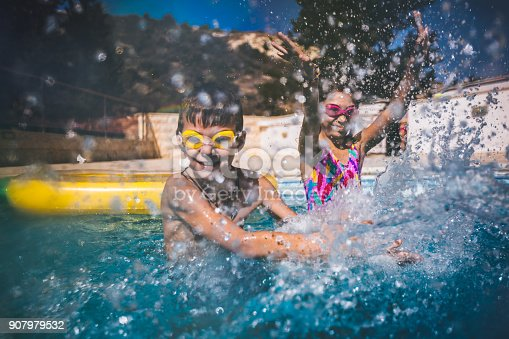 Young brother and sister on family summer vacations having fun splashing water in swimming pool
