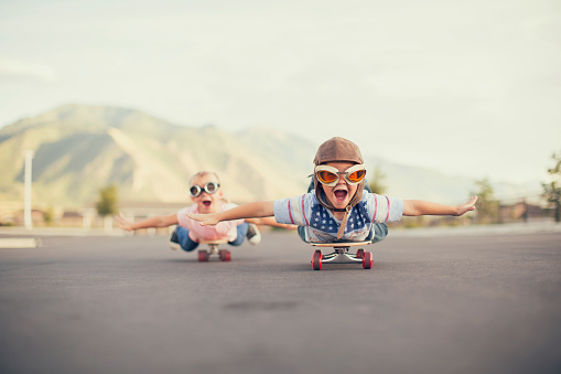 istock Young Boy and Girl Imagine Flying On Skateboard 495731108