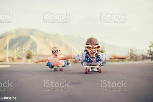Young boy and girl imagine flying on skateboard picture id495731108?b=1&k=6&m=495731108&s=612x612&h=zgbua1idbdaczlqiyr6mwmv85x2xrnlv93tp8cbopdy=