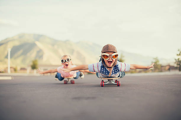Young Boy and Girl Imagine Flying On Skateboard A young boy and girl are wearing flying goggles while outstretching their arms to attempt flying while on skateboards. They have large smiles and are imagining taking off into the sky. leisure equipment stock pictures, royalty-free photos & images