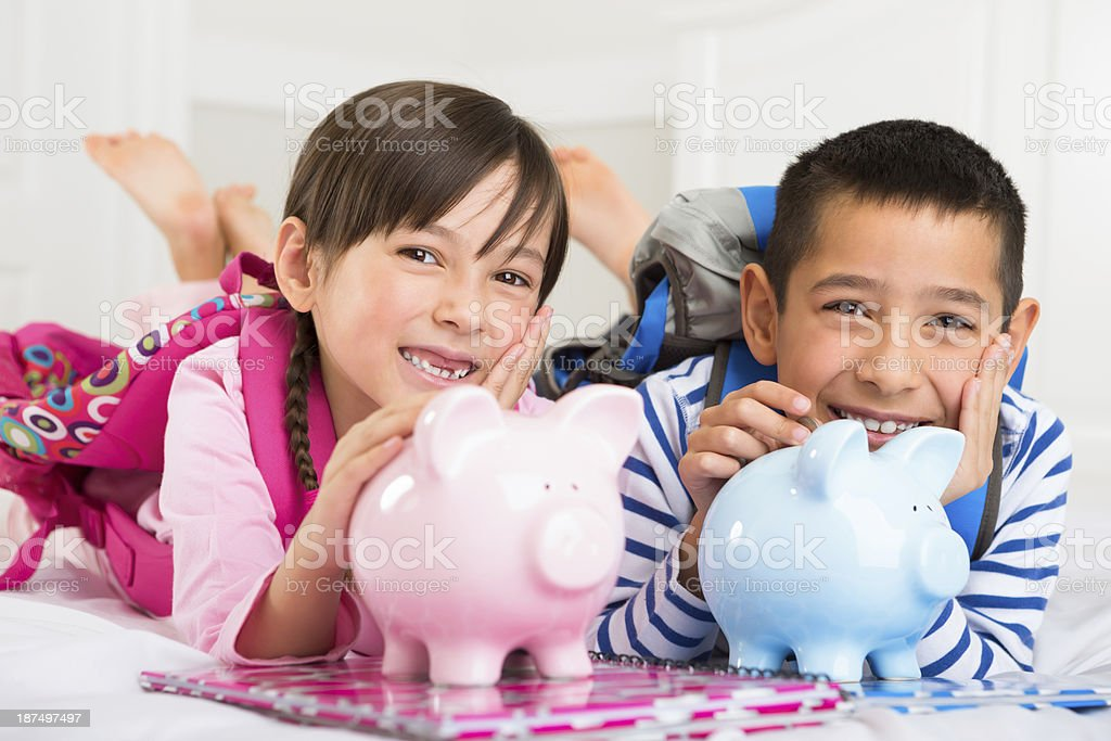 Young boy and girl playing with their piggy banks stock photo