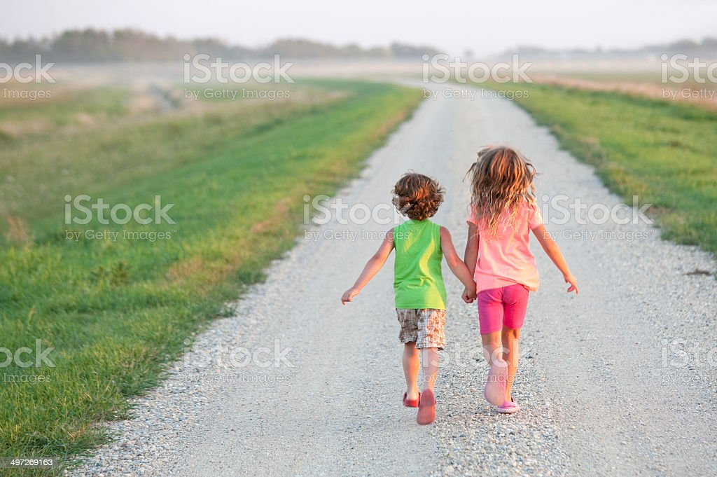 Young Boy and Girl Running Down Gravel Road stock photo