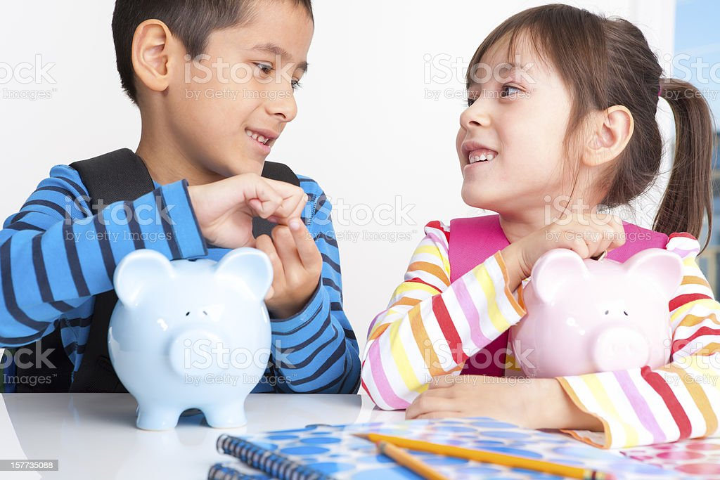 Young boy and girl saving money for school stock photo