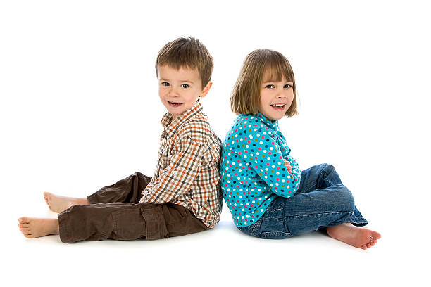 Young boy and girl sitting back to back on white stock photo