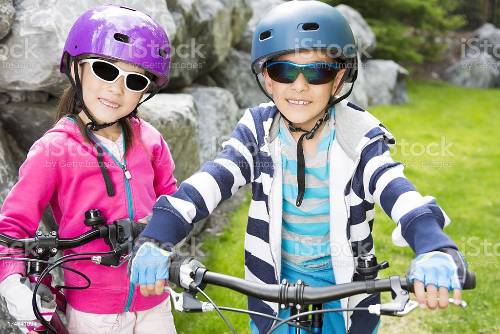 Young boy and girl taking a quick break from bicycling royalty-free stock photo