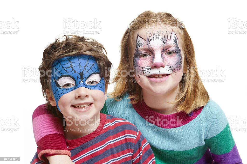 Young boy and girl with face painting cat superhero stock photo