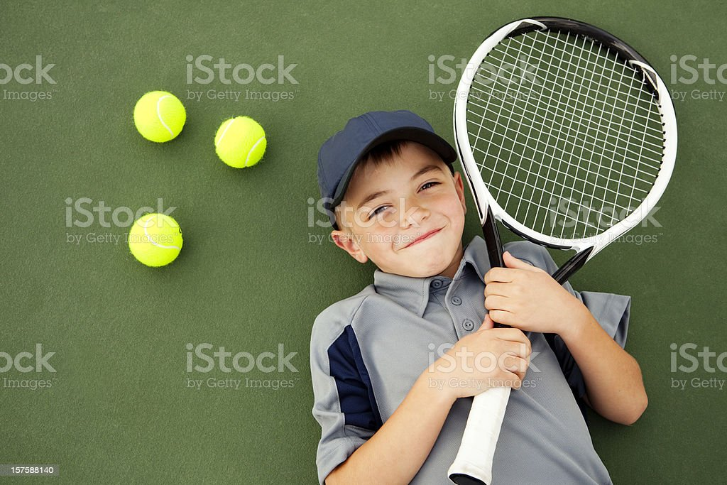 Young Boy and Tennis Player Lying Down on Tennis Court royalty-free stock photo