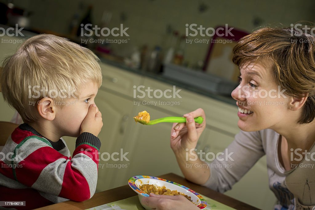 Young boy applies Hand Over Mouth technique to avoid lunch stock photo