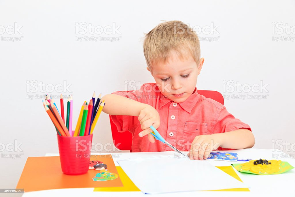 Young boy at a desk with art supplies cutting paper stock photo