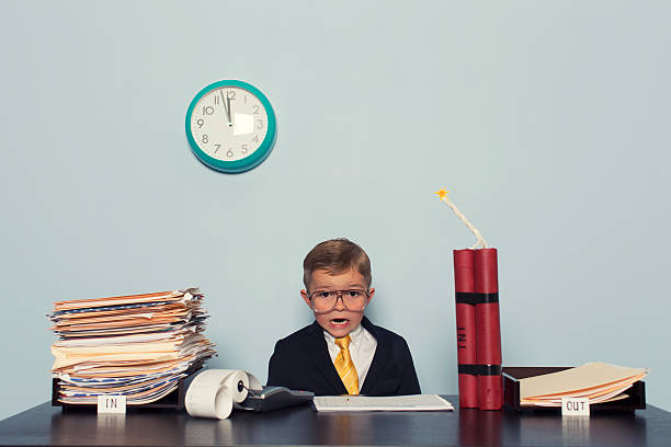 Young Boy at Business Desk Awaits Deadline stock photo