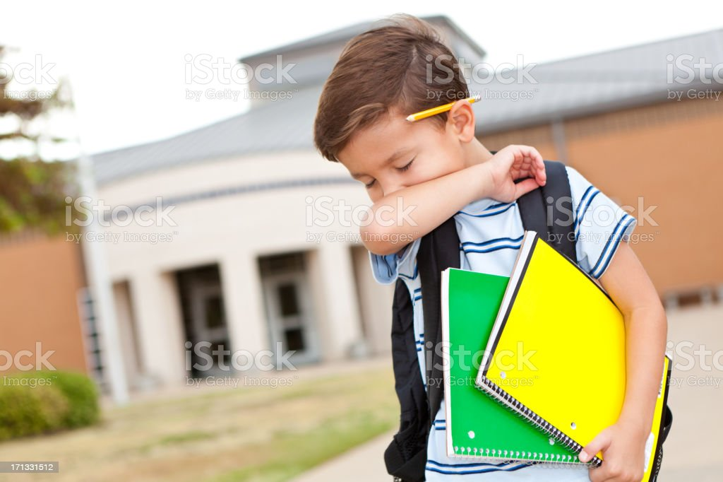 Young boy at school coughing into his arm stock photo
