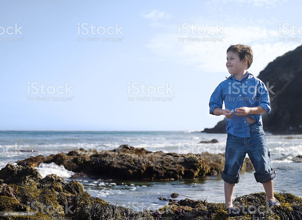 Young boy (6-7) at seashore, Sonriendo foto de stock libre de derechos