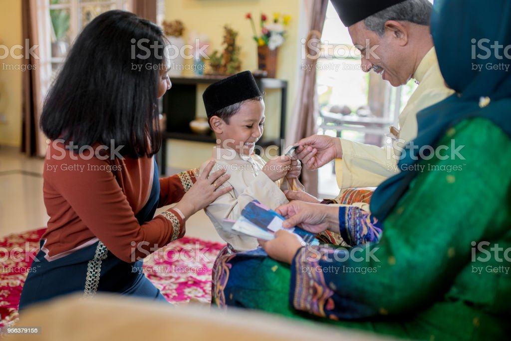Young boy being presented with a gift of money from his grandparents as part of the Islamic celebration of Hari Raya Aidilfitri (Eid al-Fitr) stock photo