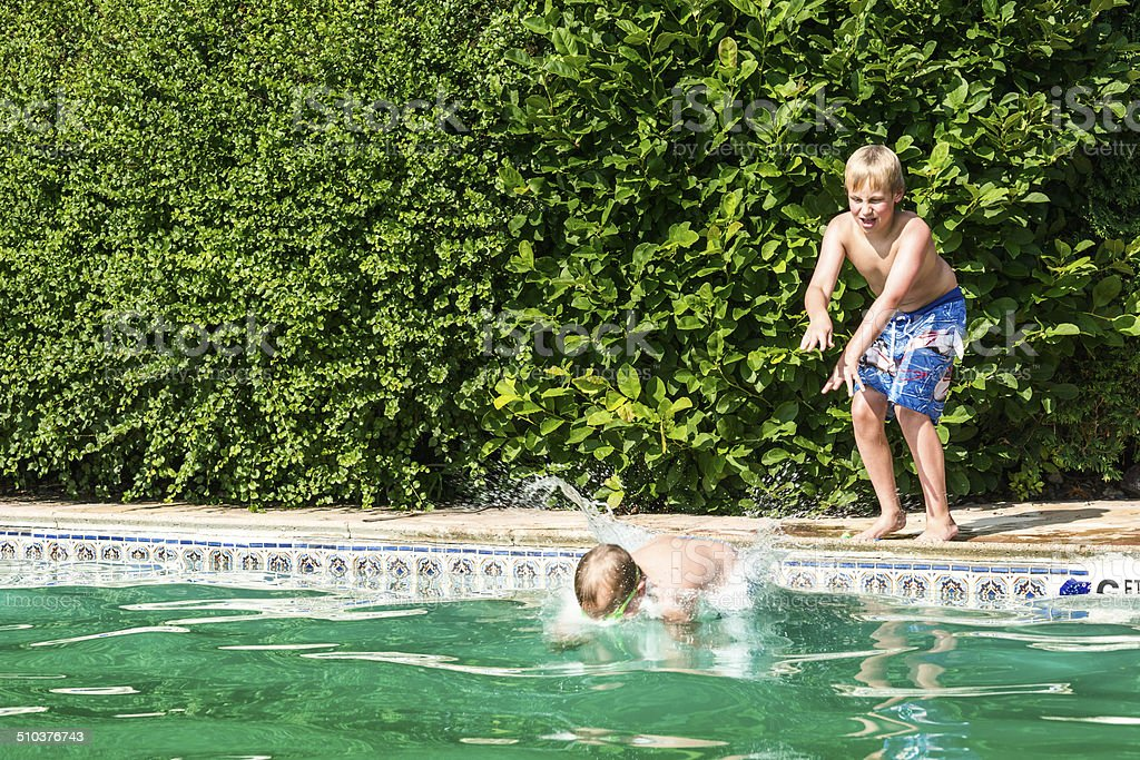 Young boy belly flops into pool stock photo