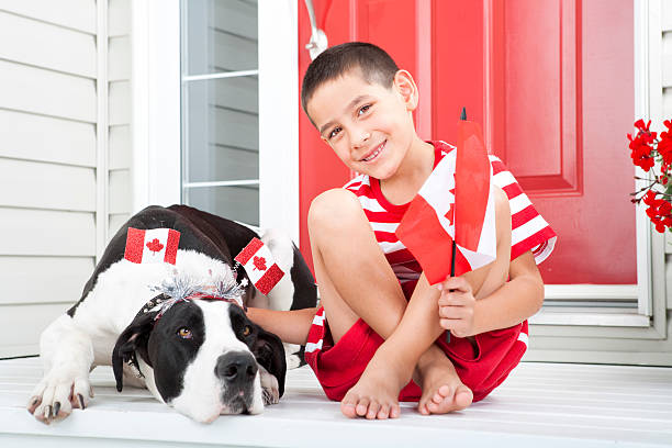 young boy bonding with his dog on canada day - canada day stock pictures, royalty-free photos & images