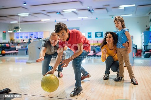 Family looking at the boy bowling