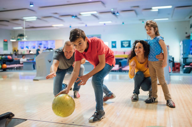 Young boy bowling with family stock photo