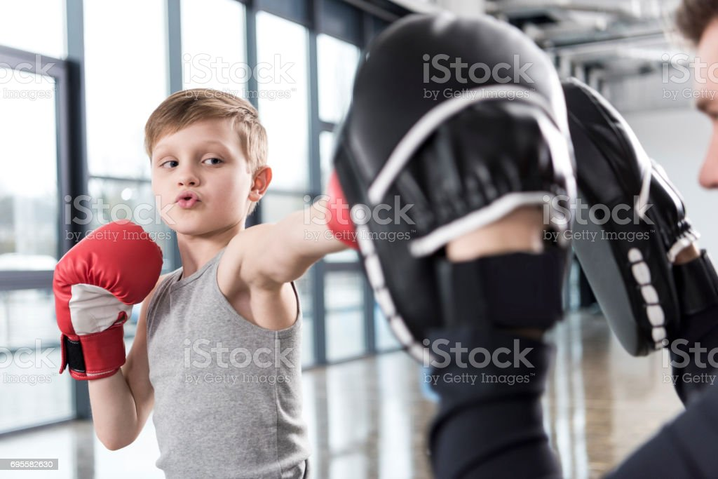 young boy boxer practicing punches with coach stock photo