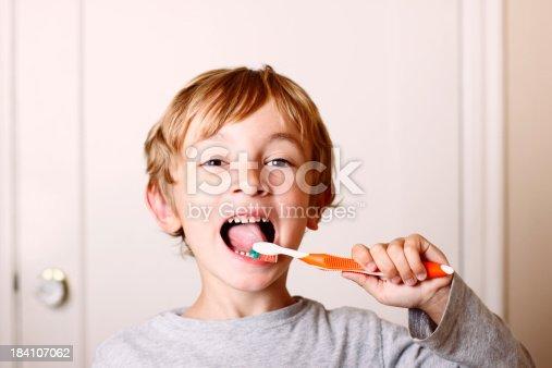 istock Young boy brushing his teeth with orange toothbrush  184107062