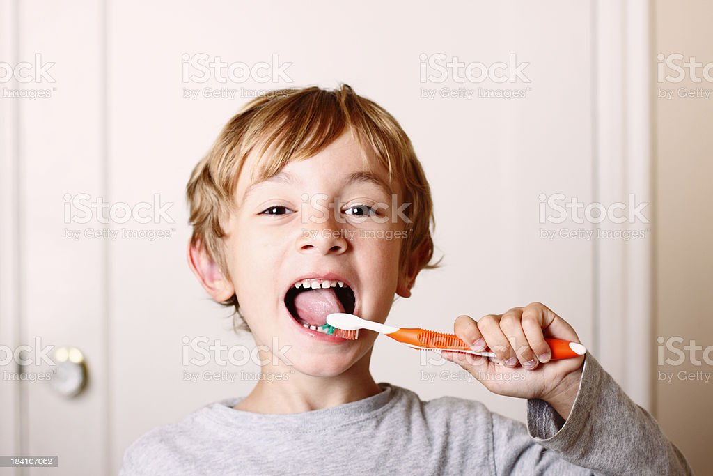 Young boy brushing his teeth with orange toothbrush  stock photo