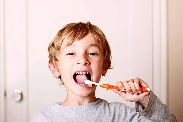 Young boy brushing his teeth with orange toothbrush
