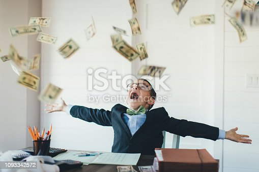 istock Young Boy Businessman Catching Falling Money 1093342572