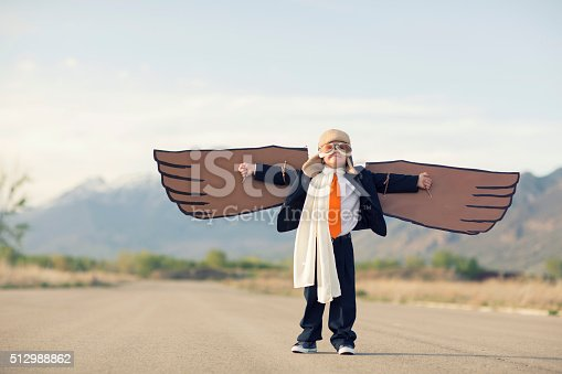 A young business boy dressed in suit, tie and flying goggles holds his cardboard bird wings to the sky. He is dreaming of flying and becoming a pilot. Image taken in Utah, USA.
