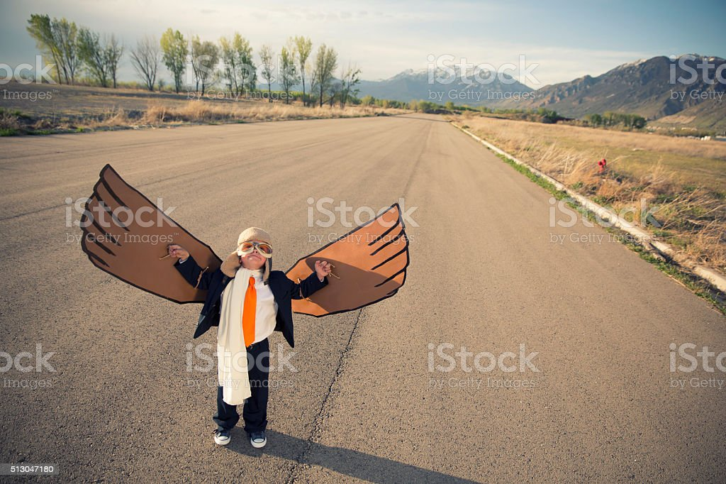 Chico joven hombre de negocios en traje decorado con alas de cartón - foto de stock