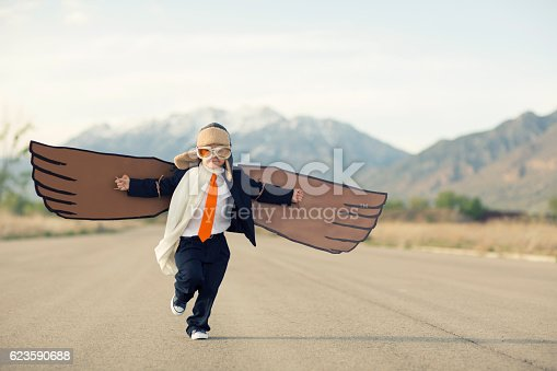 A young business boy dressed in suit, tie and flying goggles runs with his cardboard bird wings to the sky. He is dreaming of flying and becoming a pilot. His business is flying. Image taken in Utah, USA.