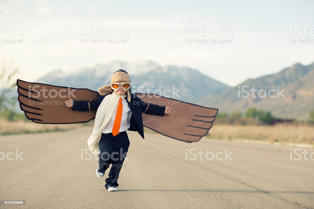 Young Boy Businessman Dressed in Suit with Cardboard Wings​​​ foto