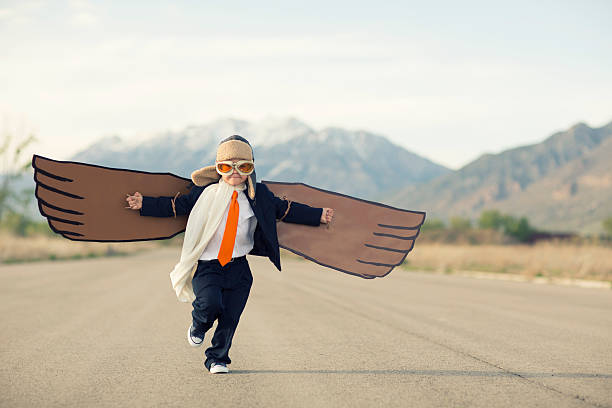 young boy businessman dressed in suit with cardboard wings - obstacle run stockfoto's en -beelden