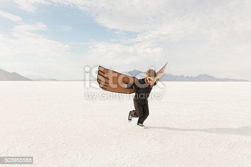 A young business boy dressed in business suit wearing cardboard wings and aviator goggles is ready to fly his business into the sky. He is running on the Bonneville Salt Flats in Utah, USA.