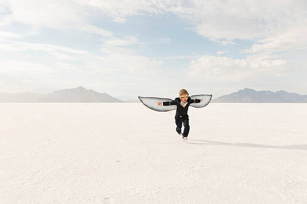 Young Boy Businessman is Flying Away A young business boy dressed in business suit and wearing cardboard wings and aviator goggles is ready to fly his business into the sky. He is running on the Bonneville Salt Flats in Utah, USA. bonneville salt flats stock pictures, royalty-free photos & images