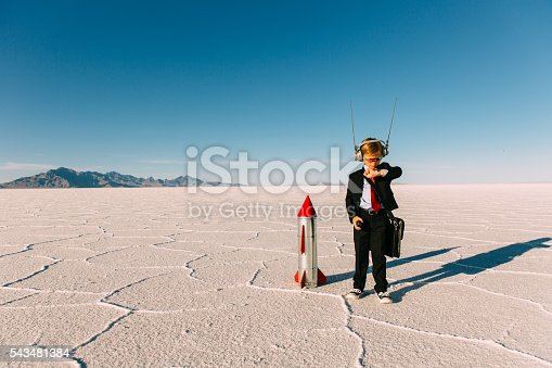 A young boy dressed in a business suit and tie stands on the Bonneville, Utah Salt Flats waiting for his new business and rocket to launch. He is wearing sunglasses and counting down to lift off while looking at his watch. The sky is blue and there is lots of copy space.