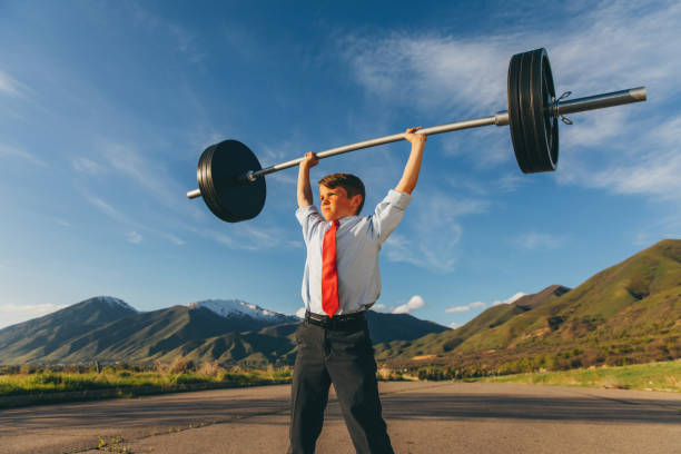 Young Boy Businessman Lifting Weights stock photo