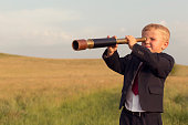 istock Young Boy Businessman Looking through Telescope 491428626