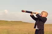 istock Young Boy Businessman Looking throught Telescope 491311428