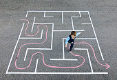 A young business boy and businessman wearing business attire is running the wrong way through a maze. He is confused and doing it the incorrectly, going backwards through the business market. He is finding the more problems to overcome for his small business to succeed.