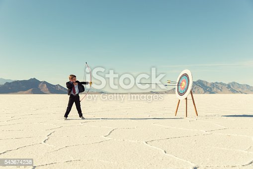 844638658 istock photo Young Boy Businessman Shoots Arrows at Target 543674238